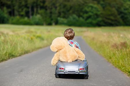 Wenig Vorschulkind Junge, der großen Spielzeugauto fahren und Spaß haben mit mit seinem Plüschspielzeugbären spielen, im Freien. Kind genießen warmen Sommertag in der Natur Landschaft