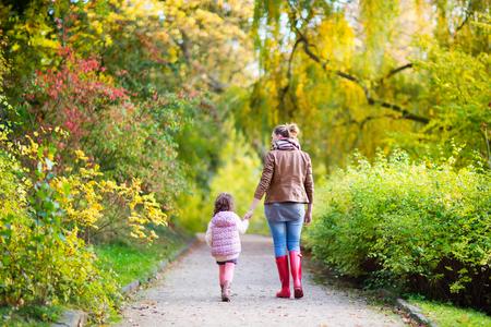 rain boots: joven madre y su peque�a hija en el parque hermoso del oto�o. muchacha ni�o y de la mujer hermosa en botas de goma para caminar y que se divierten. retrato de familia al aire libre.