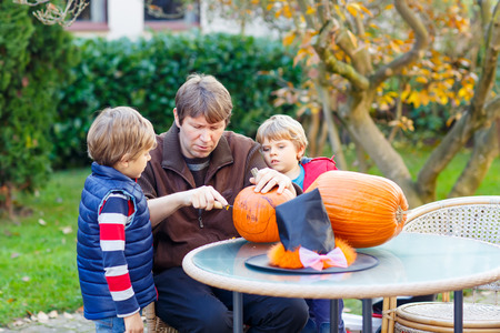 Young dad and two little kid boys making jack-o-lantern for halloween pumpkin in autumn garden, outdoors. Father and children Family having fun together