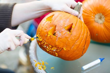 feld: Hollowing out a scary pumpkin to prepare halloween lantern. Jack-o-lantern. Hands with knife and feld pen Stock Photo