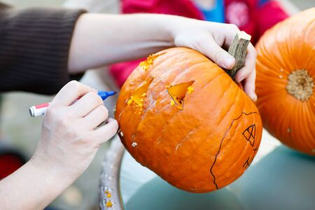 Hollowing out a scary pumpkin to prepare halloween lantern. Jack-o-lantern. Hands with knife and feld pen Stock Photo