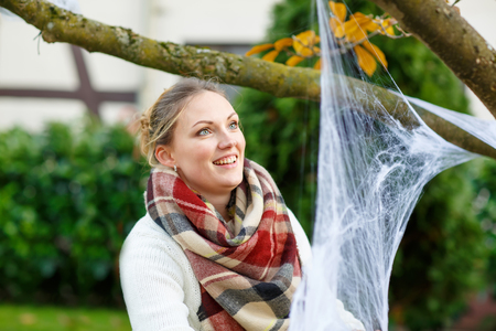 home decorating: Young woman decorating home garden for halloween with spider web. Family celebrating holiday. Stock Photo