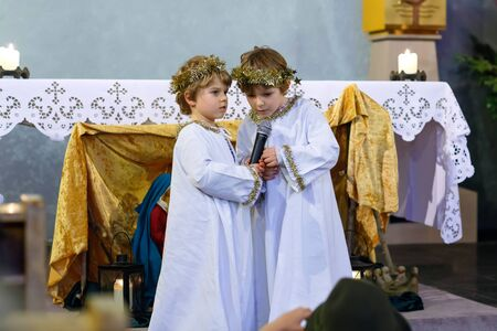christmas story: Two little kid boys playing angels in Christmas story in a church. Happy adorable blond children