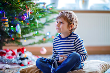 depending: Cute little blond kid boy playing with a video game console on Christmas with decorated tree on background. Child having fun at home.