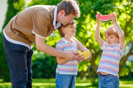 3 5 years: Two little preschool kid boys and father eating red and yellow watermelon in summer garden. Funny happy children and dad smiling. healthy fruit snack on sunny day.