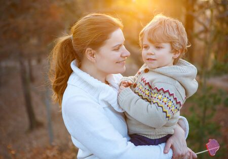 Mother and little son in park or forest, outdoors. Hugging and having fun together. photo