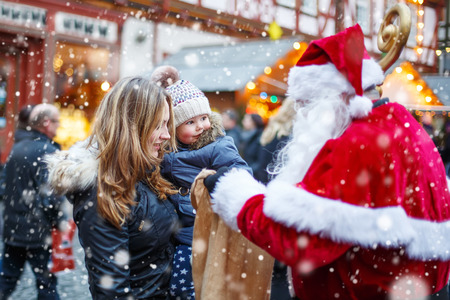 Cute toddler girl with mother on Christmas market. Funny happy kid taking gift from bag of Santa Claus. holidays, christmas, childhood and people concept. Happy family during snowfall on winter day. Banque d'images