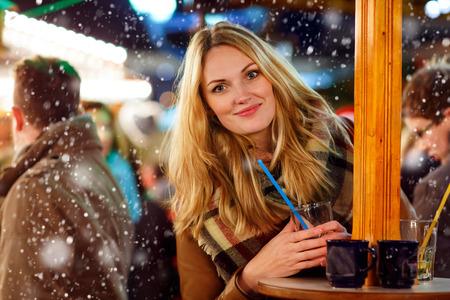 Krásná mladá žena pít horký punč, svařené víno na německý vánoční trh. Šťastná dívka v zimním oblečení se světly na pozadí. Rodina, tradice, svátek koncepce