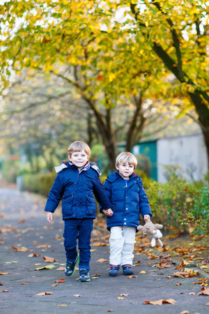 Active two little funny kid boys walking together in a park on sunny autumn day. Happy, joyful family of two. Sibling twins having fun