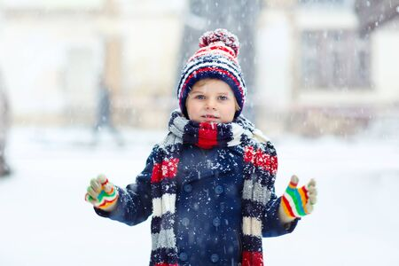 having fun in the snow: Winter portrait of little kid boy in colorful clothes, outdoors during snowfall. Active outoors leisure with children in winter on cold snowy days. Happy child having fun with snow