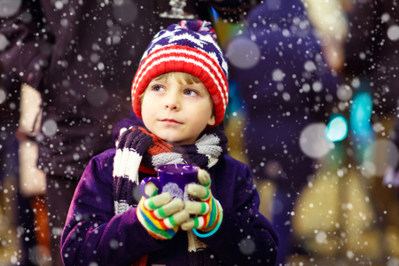 weihnachtsmarkt: Little cute kid boy with cup of steaming hot chocolate or children punch. Happy child on Christmas market in Germany. Traditional leisure for families on xmas Stock Photo