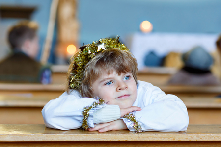 christmas story: Adorable toddler, little kid boy playing an angel in Christmas story in a church. Happy adorable blond child with lights and xmas tree on background.