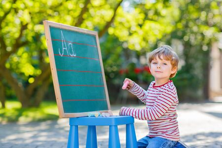 Adorable funny little kid boy at blackboard practicing writing letters, outdoor school or nursery. Child having fun with learning. Back to school concept. Stock Photo