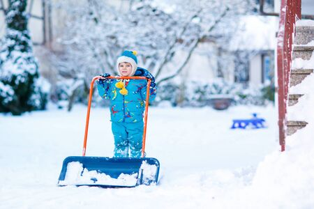 Cute little kid boy in colorful winter clothes having fun with snow shovel, outdoors during snowfall. Active outdoors leisure with children