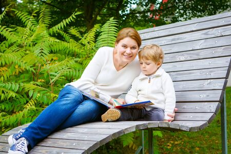 Little preschool boy and his mother sitting on bench in park and reading fairytale book together. photo