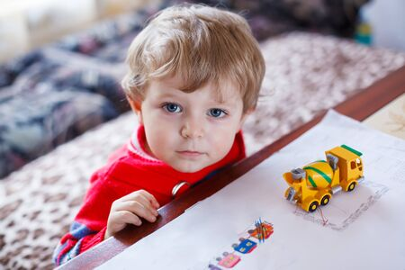 inddor: Little toddler boy with blue eyes playing with toy, inddor