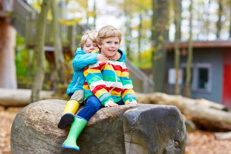 kiddies: Two little kid boys in colorful rain jackets and gumboots having fun with playing on forest playground on warm, autumn day, outdoors. Siblings hugging and laughing together.