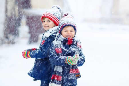 having fun in the snow: Two little kid boys in colorful clothes, outdoors during snowfall. Active outoors leisure with children in winter on cold snowy days. Happy siblings having fun with snow Stock Photo