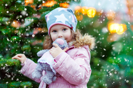 Cute little smiling kid girl with christmas tree. Happy child in winter clothes and toy choosing xmas tree on Christmas market with lights on background. Family, tradition, celebration concept Stock Photo