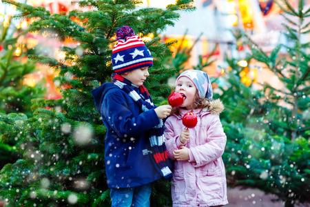 Twee kleine lachende kinderen, jongen en meisje die uitgekristalliseerd gesuikerde appel op Duitse kerstmarkt. Gelukkige kinderen in de winter kleding met lichten op de achtergrond. Familie, traditie, vakantieconcept