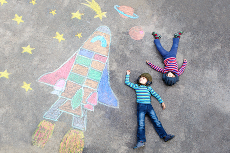 friends having fun: Two Funny little kid boys flying in universe by a space shuttle picture painting with colorful chalks. Creative leisure for children outdoors in summer. Friends having fun together Stock Photo