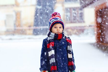 outoors: Winter portrait of little kid boy in colorful clothes, outdoors during snowfall. Active outoors leisure with children in winter on cold snowy days. Happy child having fun with snow