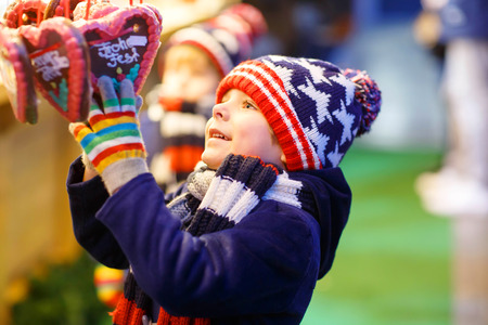 Little cute kid boy happy about gingerbread cookies hearts. Happy child on Christmas market in Germany. Traditional leisure for families on xmas