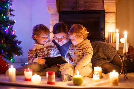 Young mother and his two little children sitting by a fireplace at home on Christmas time. Kids boys playing with tablet. Through window from outdoors photo