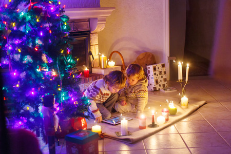 sibling: Two little sibling boys sitting by a fireplace at home on Christmas time with a surprise gift. Kids playing with new tablet. Through window from outdoors