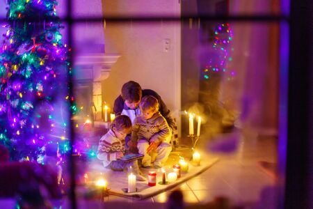 Young father and his two little children sitting by a fireplace at home on Christmas time. Kids boys playing with tablet. Through window from outdoors photo