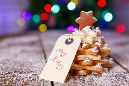 Home made baked Christmas gingerbread tree as a gift for family and friends on wooden background. With colorful lights from Christmas tree on background. With icing sugar als snow. Selfmade gift for xmas. Standard-Bild