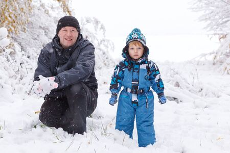 Little preschool boy and his father playing with first snow in forest photo