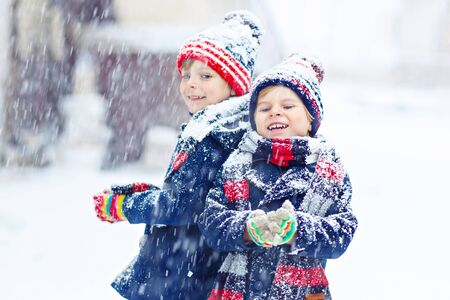 outoors: Two little kid boys in colorful clothes, outdoors during snowfall. Active outoors leisure with children in winter on cold snowy days. Happy friends having fun with snow