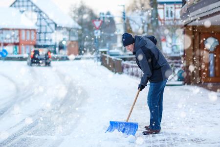 雪のシャベルを持つ男は、冬の歩道をクリーンアップします。ヨーロッパの冬時間。暖かい冬の服の若い男