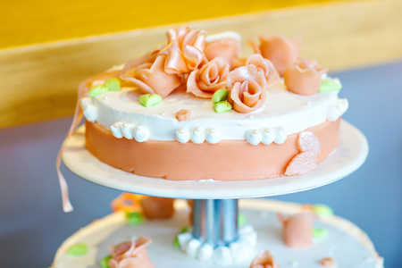 wedding cake with soft flowers, in white and orange Stock Photo
