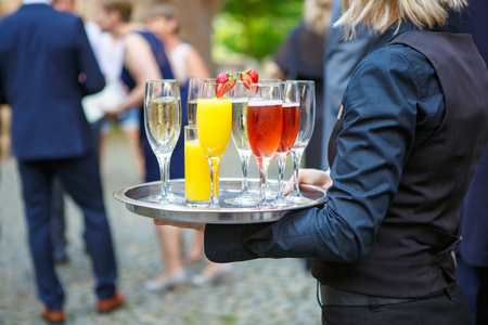 wedding feast: A waiter or waitress with a tray of glasses of champagne, delicious punch and glasses of orange juice at the wedding reception. Glasses with alcohol and different drinks