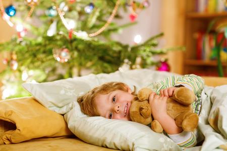 niño durmiendo: Adorable niño rubio que duerme con el oso de peluche bajo el árbol de Navidad y soñando con Santa en casa, en el interior. Niño feliz muchacho que espera regalos. Foto de archivo