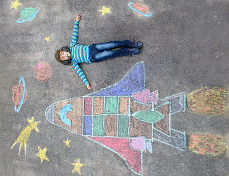 Funny little kid boy flying in universe by a space shuttle picture painting with colorful chalks. Creative leisure for children outdoors in summer. Imagens