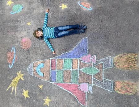 Grappig klein kind jongen vliegen in het universum door een space shuttle foto schilderij met kleurrijke krijt. Creatieve vrijetijdsbesteding voor kinderen buiten in de zomer.