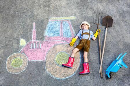 rain boots: ni�o peque�o ni�o feliz en botas sombrero de paja y de lluvia que se divierten con la imagen del tractor dibujo con tizas de colores. Los ni�os, estilo de vida, concepto de diversi�n. Ni�o de sue�o del futuro y profesi�n.