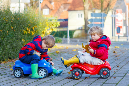 Two little kids boys in colorful clothes and rain boots driving toy cars and making competition, outdoors. Active leisure for friends on autumn day