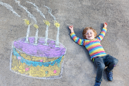 Happy little kid boy having fun with big birthday cake picture drawing with colorful chalks. Creative leisure for children outdoors in summer. Child celebrating birthday. Stock Photo