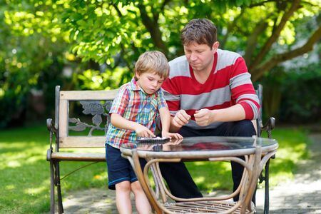 Little kid boy and his young father playing together checkers. Dad teaching his son to play thinking game. Family having fun in summer garden outside.
