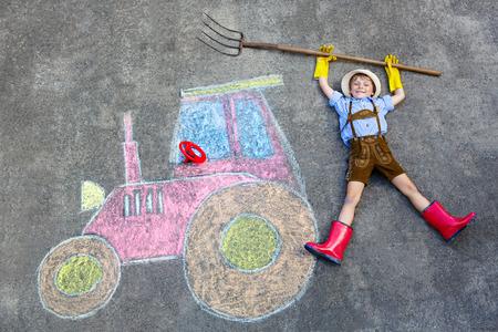 botas de lluvia: ni�o peque�o ni�o feliz en botas sombrero de paja y de lluvia que se divierten con la imagen del tractor dibujo con tizas de colores. Los ni�os, estilo de vida, concepto de diversi�n. Ni�o de sue�o del futuro y profesi�n.