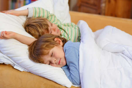 sibling: Two little blond sibling boys sleeping in bed. Tired kids dreaming and relaxing. Happy family of two brothers.