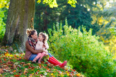 beautiful young mother and her little daughter hugging at beautiful autumn forest. Kid girl and woman playing with yellow and red maple foliage. Family portrait, fall season.