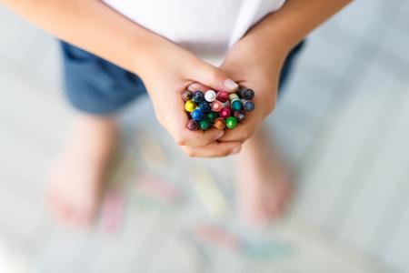 Primer plano de las manos del niño con una gran cantidad de colores de cera lápices de colores lápices. Kid preparación de material de papelería y el estudiante. Volver al concepto de escuela