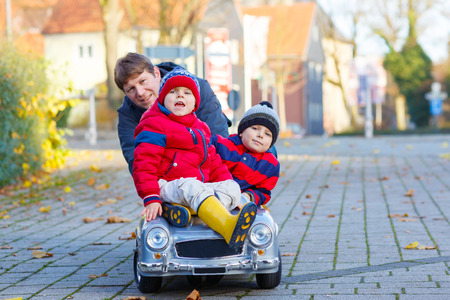 Two little kids boys in colorful clothes and happy dad driving old car. Father and sons making competition, outdoors. Active leisure for family on autumn day photo