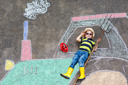 Happy little child of four years having fun with tractor picture drawing with chalk.
