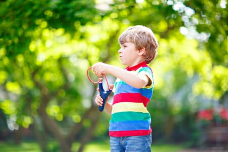 dowdy: Funny little kid boy shooting wooden slingshot against green tree background. Child having fun in summer.